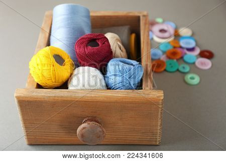 Wooden drawer with sewing threads and crocheting clews on grey background