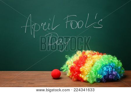 Clown nose and rainbow wig on table near chalkboard with written phrase