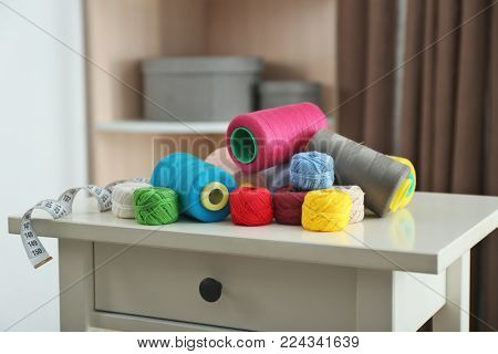 Sewing threads and crocheting clews on small table indoors