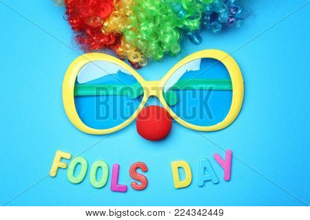 Big glasses, clown nose and rainbow wig on color background. April fool's day celebration