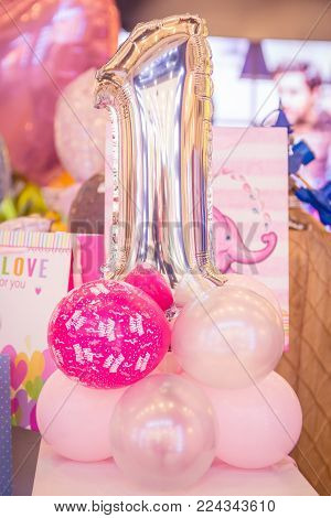 Pink helium birthday balloons for baby girls. First birthday party.