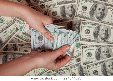Cash in hand. Profit, savings. Stack of dollars. a person who is counting money against the background of money, success, motivation, financial flows, wealth. Buy dollars, dollars manually.
