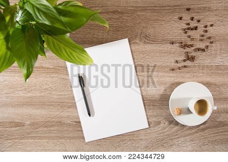 espresso in white cup with sweet nutty treat on wooden table decorated with plant green leaves brown coffee beans and empty white paper and pen ready to take notes