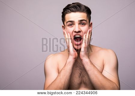 Young Handsome Man Applying Aftershave Face Cream Isolated On Gray Background