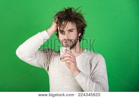 Man Drink Pill With Water From Glass, Has Uncombed Hair In Morning On Green Background, Health And M