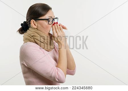 Sick woman holding a handkerchief, white background