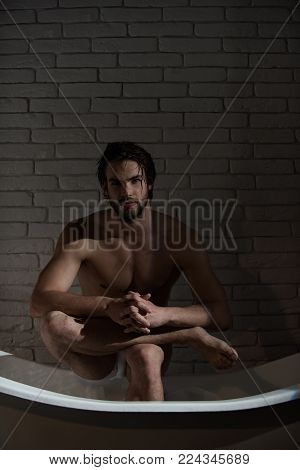 Hygiene and healthcare. Guy with wet hair sitting in bath tub. Spa and relaxation, sexy man. Bathroom and home comfort. Man with muscular body in bath.