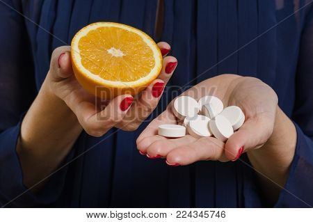 A woman holds a natural vitamin-orange in one hand and a synthetic vitamin C in the other. Makes a choice