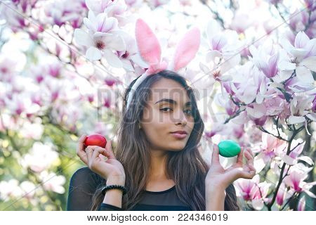 Blossoming Magnolia Flowers On Sunny Day On Floral Background And Woman Or Pretty Girl With Rosy Bun