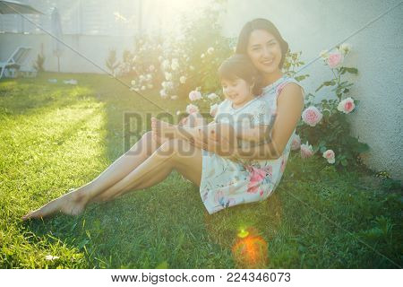 Mom And Child Smiling At Blossoming Rose Flowers. Woman With Baby Girl Sitting On Green Grass. Famil