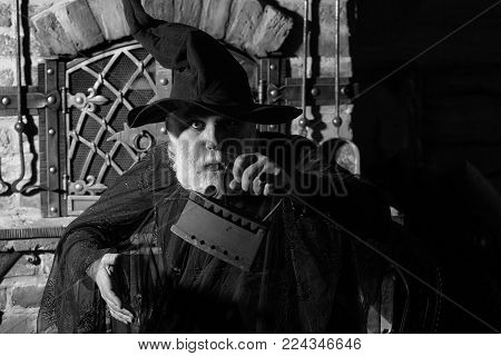 Old wizard with rusty coal iron in black costume and hat for Halloween on kitchen background