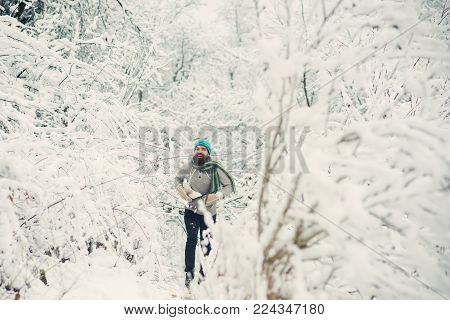 Temperature, freezing, cold snap, snowfall. Bearded man with skates in snowy forest. skincare and beard care in winter. Man in thermal jacket, beard warm in winter. Winter sport and rest, Christmas.