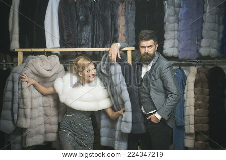 Man and girl with excited face choose furry coats on clothes rack background. Shop assistant with beard and woman select furry coat. Woman tries expensive sable overcoats. Elegance and glamour concept
