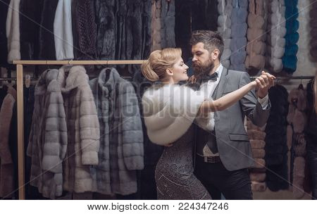 Man and woman with coats in fur shop. Money and style concept. Woman in fur coat with bearded man. dance