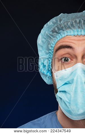 Close up half portrait of a surprised male surgeon's face wearing face mask and sterile hat isolated over dark background