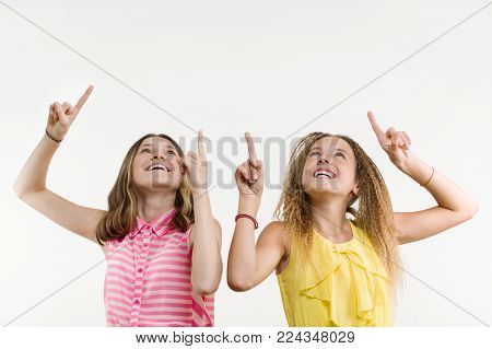 Attractive positive two teenage girl pointing her index finger up, indicating copy space on white blank wall for your content or information information