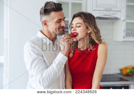 Portrait of a young romantic smart dressed couple eating strawberry while standing on a kitchen at home
