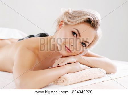 Young, beautiful and healthy woman relaxing in spa salon. Rejuvenation therapy and massage treatments. Recreation concept.