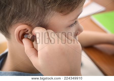 Little boy inserting hearing aid, closeup
