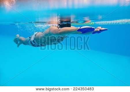 caucasian sportsman swimming with shoulder blades for swimming in the swimming pool underwater