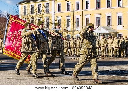 Uzhgorod, Ukraine - January 30, 2018: Honor guard carries the flag of the 128th separate mountain infantry brigade during a solemn meeting of soldiers from the ATO zone.