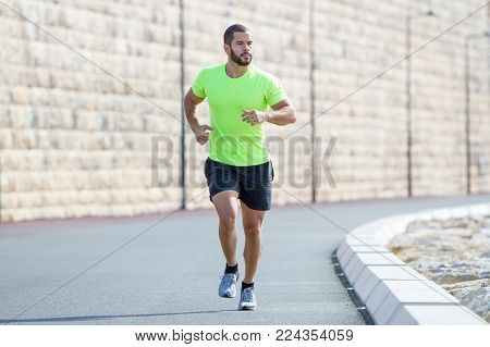 Pensive muscular young Caucasian man running along road. Handsome guy keeping fit and jogging. Sport and fitness concept