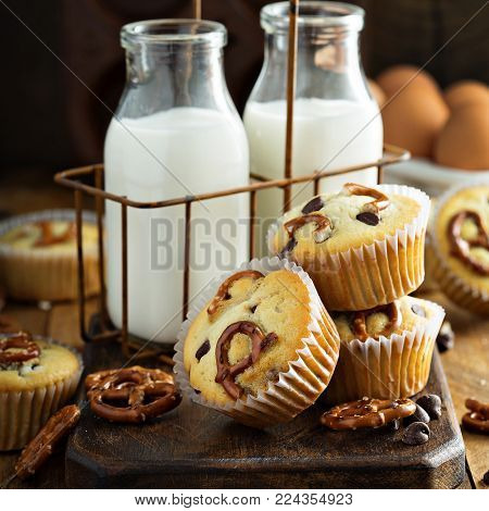 Chocolate chip and pretzel muffins with milk on wooden background for dessert