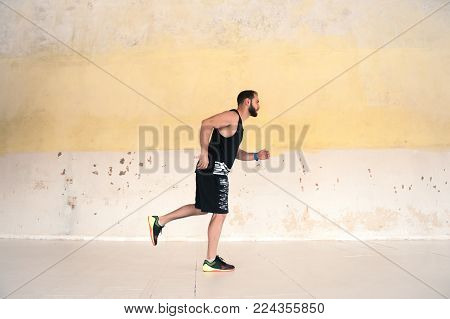 Runner sprinting against concrete wall. Morning jogging of a young athlete against a light wall