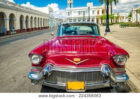 Cienfuegos , CUBA - 22 MARCH 2012 : Red Old retro Car on authentic streets Cuba Cienfuegos Vintage stylish cars since colonial era are main symbol of Caribbean country in Latin America