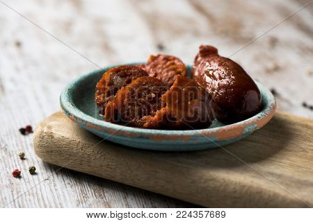 closeup of a green earthenware plate with some chopped chorizos fritos, typical spanish fried sausages, on a white rustic wooden table