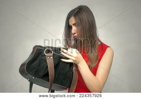 Disgruntled girl forgot her wallet with the money at home. Not enough money for shopping. The lost wallet concept.