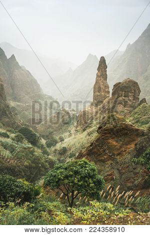 Mountain peaks of Xo-Xo valley of Santa Antao island, Cape Verde. Many cultivated plants growing in the valley between high rocks. Arid and erosion mountain peaks sun light. Sahara dust in the air.