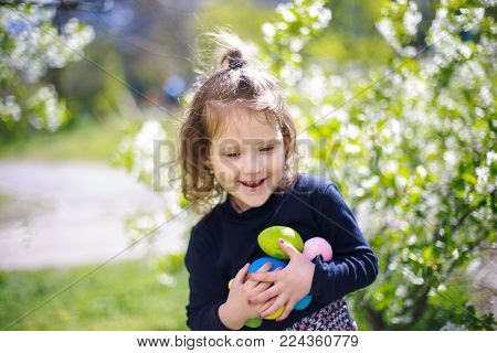 The girl is holding a collection of colorful Easter eggs. A happy child celebrates Easter. Little Girl on an Easter Egg hunt on a meadow in spring