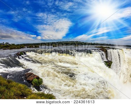 The Garganta del Diablo/ Devil's Throat is the most grandiose part of the Iguazu Falls on the Parana River. The autumn sun shines through the clouds. Concept of active and extreme tourism