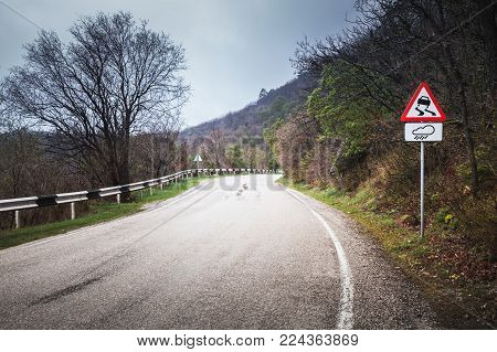 Slippery road, warning road sign stands on a mountain roadside in rainy day