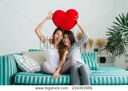 Beautiful young asian women LGBT lesbian happy couple sitting on sofa hugging and smiling together in living room at home. LGBT lesbian couple together indoors concept. Spending nice time at home.