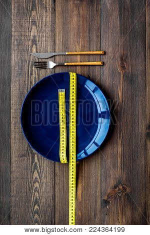 Proper nutrition for lose weight. Empty plate and measuring tape on dark wooden background top view.