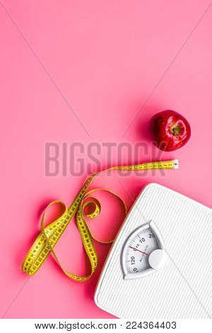 Proper nutrition for lose weight. Scale, measuring tape, apple on pink background top view space for text.