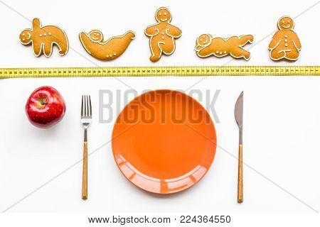 Yoga and healthy diet for lose weight. Plate and cookies in shape of yoga asans on bright white background top view.