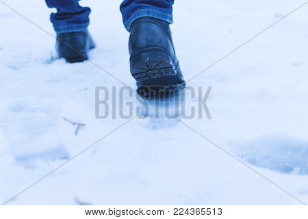 A man walks in the snow. Men's shoes. Close up