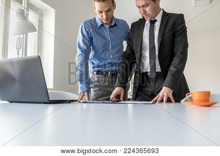 Two businessmen having a serious discussion analysing paperwork in a binder as they stand side by side at an office table in a low angle cropped view with copy space.