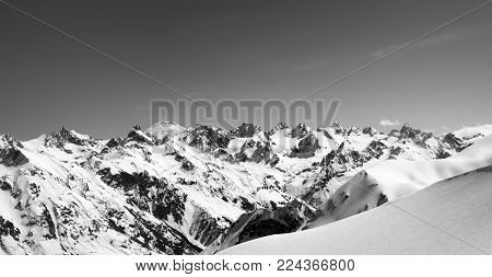 Black and white panorama of snow-capped mountains with mount Elbrus at background and off-piste snowy slope for freeride at sun cold day. View from region Dombay, Caucasus Mountains in winter.