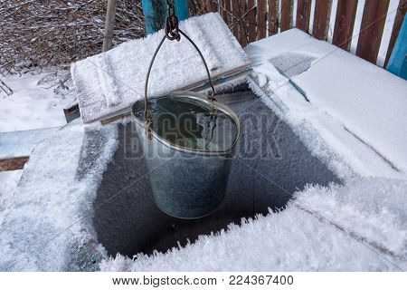 A bucket filled with clean drinking water is lifted from the well. The well is covered with a layer of fluffy snow.