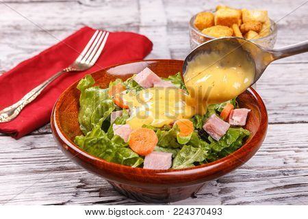 Pouring dressing on a salad. Close up of a delicious salad with honey mustard dressing.