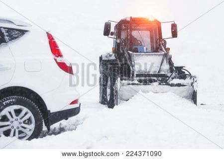 Tractor rides and cleans the road from the snow to the blizzard