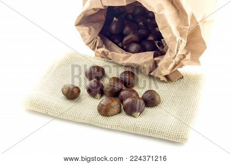 Sweet, useful, edible chestnuts (Castanea sativa) in a paper bag on a white  background close-up.