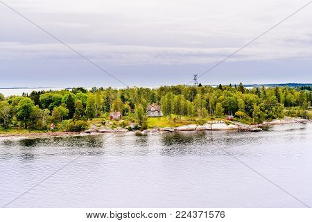Beautiful panoramic aerial view of Stockholm archipelago, Sweden. Cozy little houses and green nature. Skyline with scenery beyond the village. Summer day with clouds and deep water. Fresh nature.
