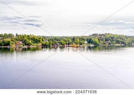 Beautiful panoramic aerial view of Stockholm archipelago, Sweden with yellow harbor and skyline with scenery beyond the city. Sunny day with blue sky, clouds and water reflection. Green nature