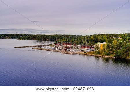 Beautiful panoramic view of Stockholm archipelago, Sweden. Stone harbor with yachts. Skyline with scenery beyond the city. Day with blue sky, clouds and water reflection. Green nature all around.