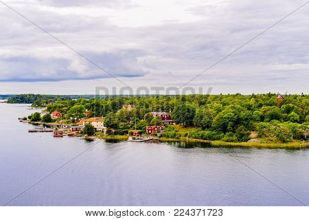 Beautiful panoramic view of Stockholm archipelago, Sweden. Cozy little houses and green nature. Skyline with scenery beyond the village. Summer day with clouds and deep water with reflection